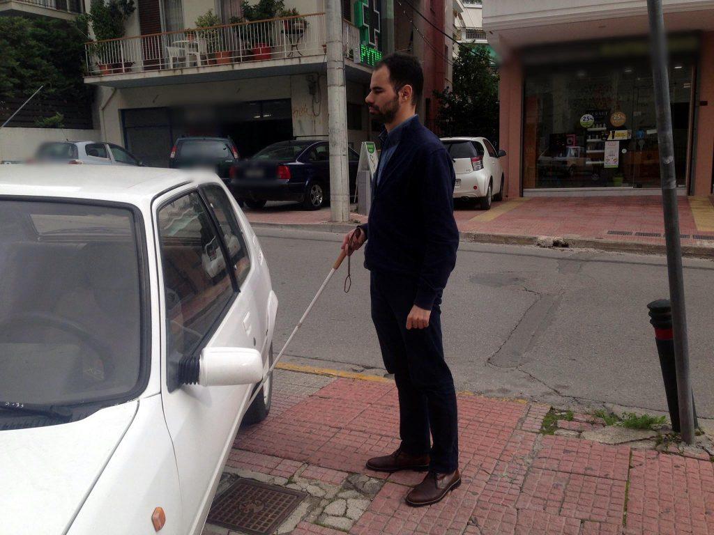 Ο Βαγγέλης Αυγουλάς βρίσκει παρκαρισμένο σε πεζοδρόμιο περπατώντας με το Λευκό Μπαστούνι