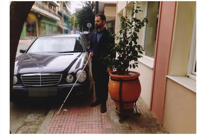 Ο Βαγγέλης Αυγουλάς περπατάει σε πεζοδρόμιο με το Λευκό Μπαστούνι και βρίσκει παρκαρισμένο και γλάστρα