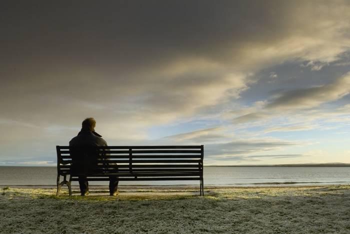 άντρας που κάθεται μόνος του σε ένα παγκάκι