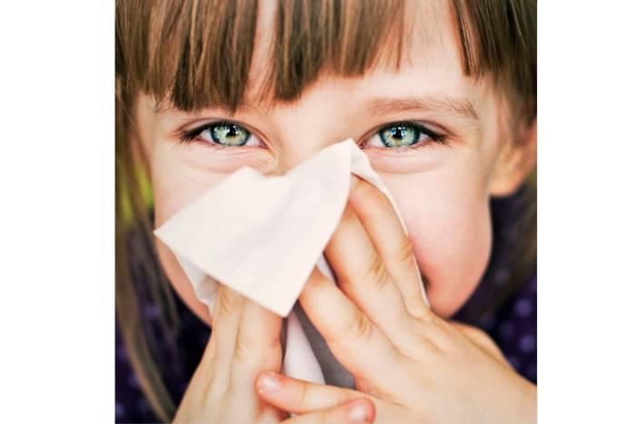 παιδί με χαρτομάντηλο φυσάει τη μύτη του