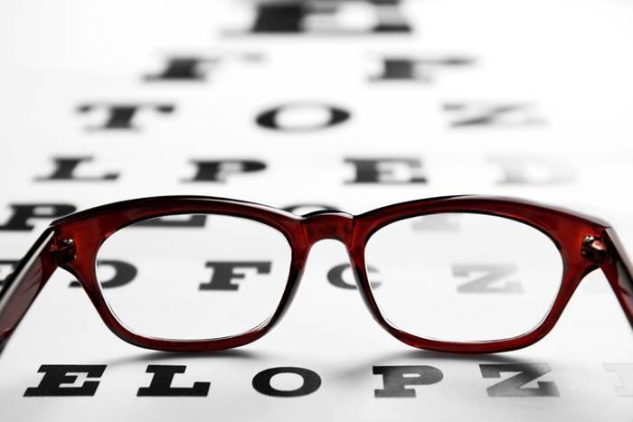 ένα ζευγάρι γυαλιών ακουμπισμένα πάνω σε ένα χαρτί με γράμματα