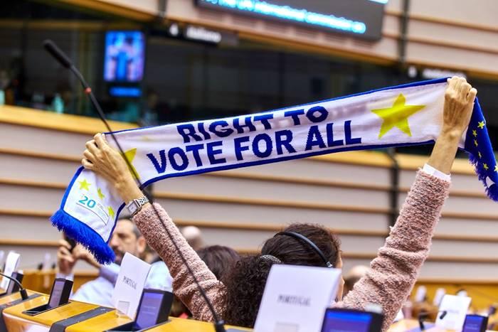 Γυναίκα που σηκώνει κασκόλ ψηλά και το κασκολ γράφει δικαίωμα ψήφου για όλους