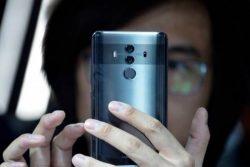 ένας άντρας κρατάει το κινητό μπροστά στο πρόσωπο του και η εφαρμογή χαρτογραφεί τα χαρακτηριστικά του