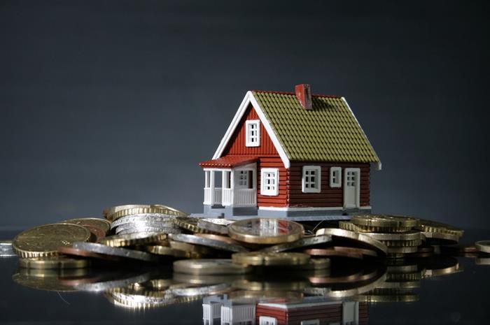 πλαστικό σπίτι πάνω σε κέρματα