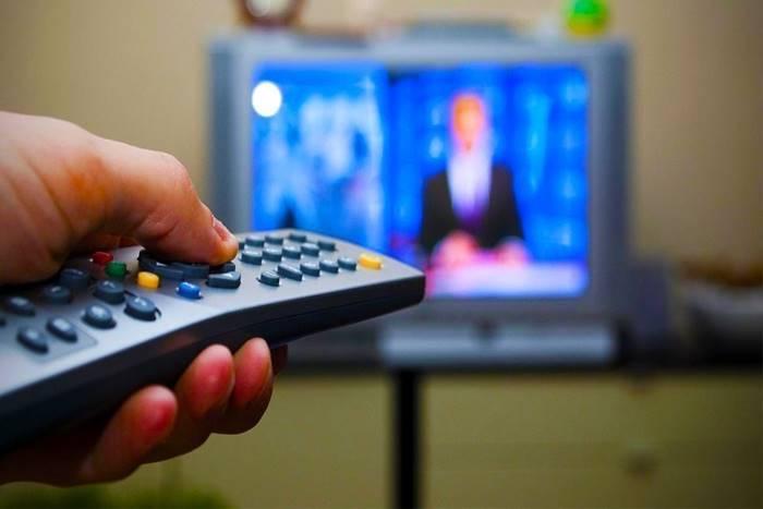 Χέρι με τηλεκοντρολ και τηλεόραση απέναντι