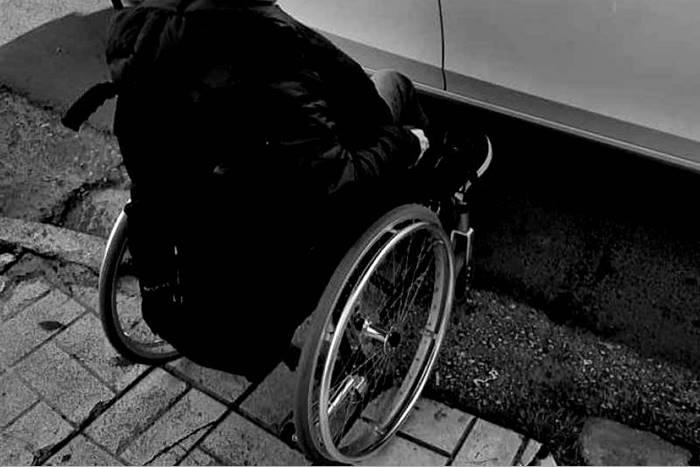 άνθρωπος σε αμαξίδιο που δεν μπορεί να κατέβει από το πεζοδρόμιο επειδή υπάρχει παρκαρισμένο αυτοκίνητο