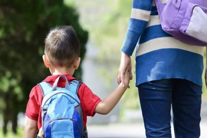 μητέρα κρατάει από το χέρι παιδί