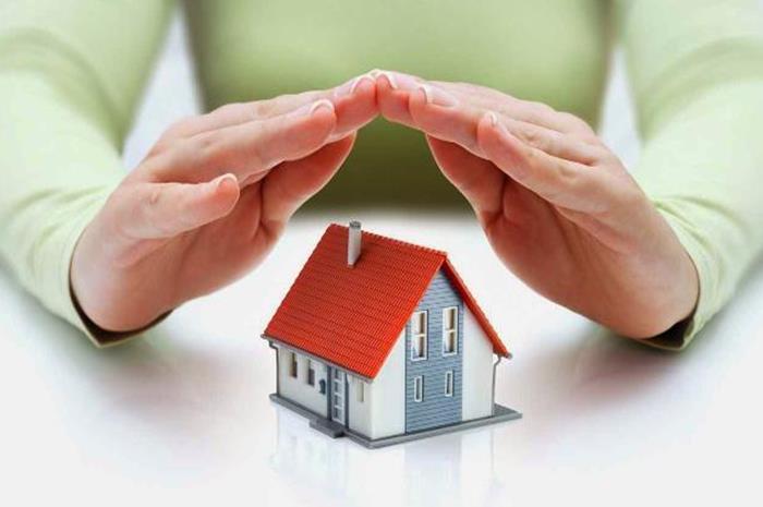 χέρια που σκεπάζουν μια προσομοίωση σπιτιού