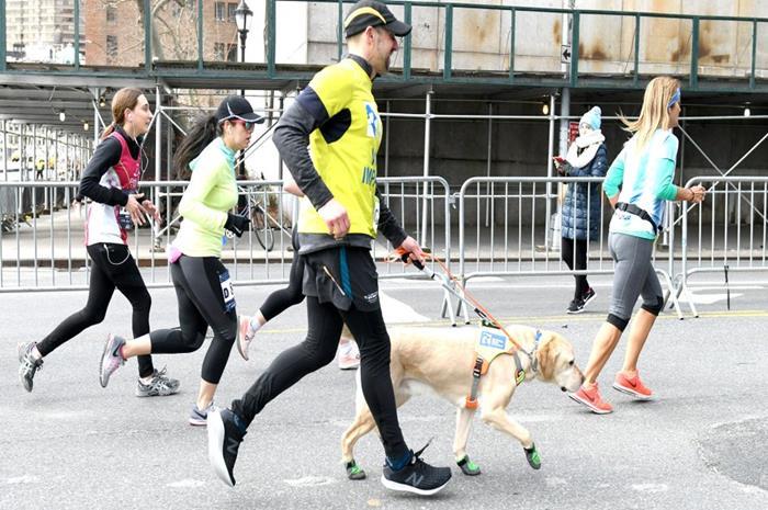ο τυφλός δρομέας τρέχει με σκύλο οδηγό