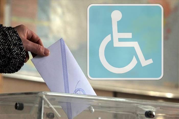 χέρι που ρίχνει στην κάλπη ψήφο και σήμα ΑμεΑ