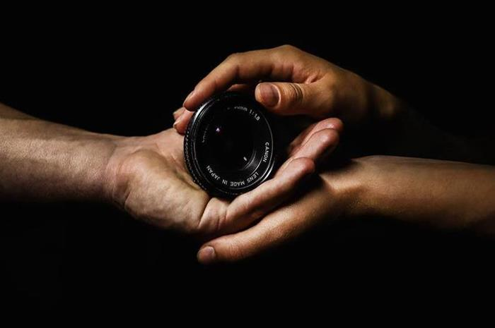 Δύο χέρια που κρατάνε ένα φακό φωτογραφικής