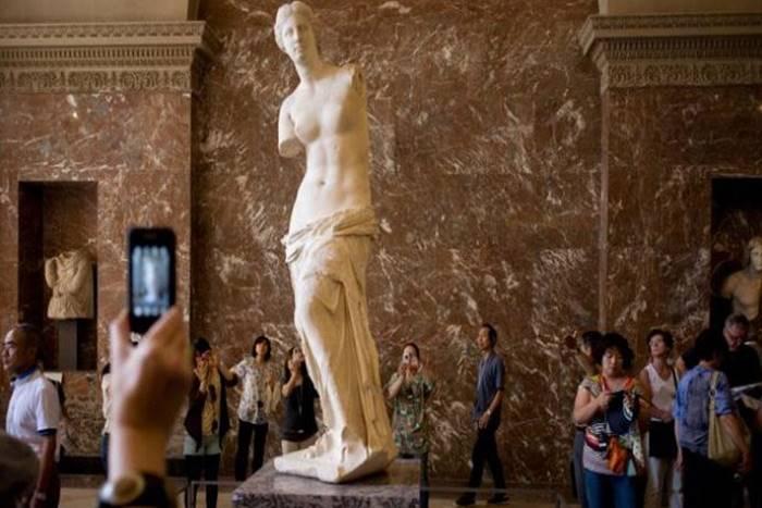 η Αφροδίτη της Μήλου στο Μουσείο του Λούβρου με επισκέπτες θαυμαστές της