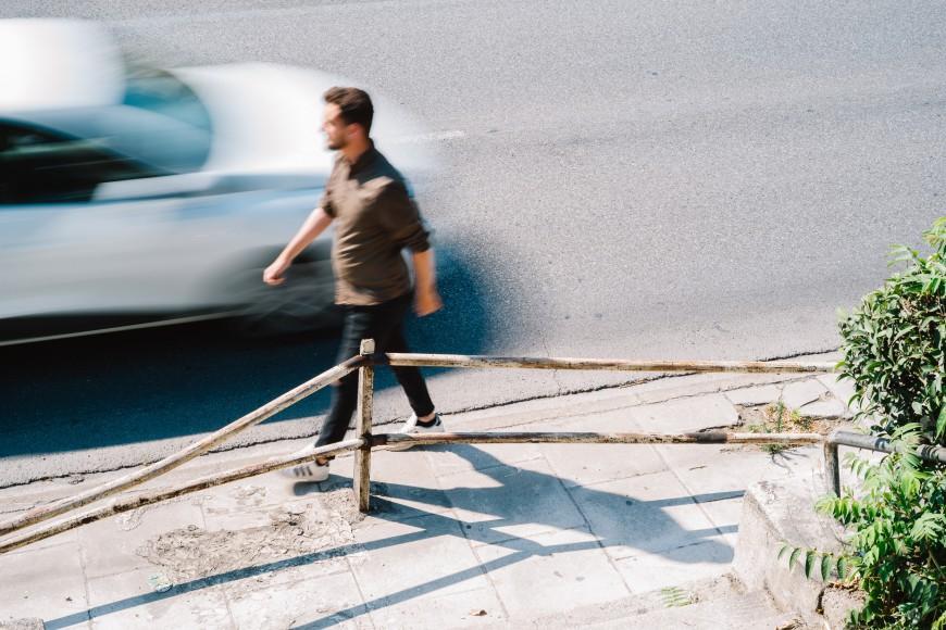 Άνδρας περπατάει σε σχεδόν ανύπαρκτο πεζοδρόμιο στη Συγγρού