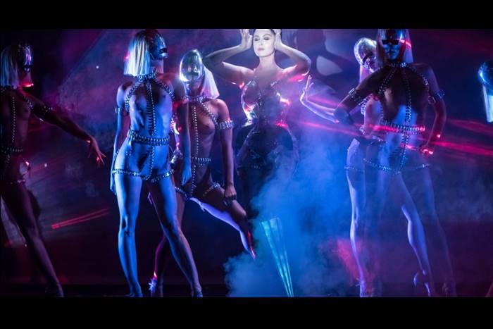 Η Βικτώρια Μοντέστα επί σκηνής πλαισιωμένη από ημίγυμνες χορεύτριες