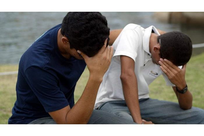 Δύο άντρες σκυμμένοι κρατάνε το κεφάλι τους