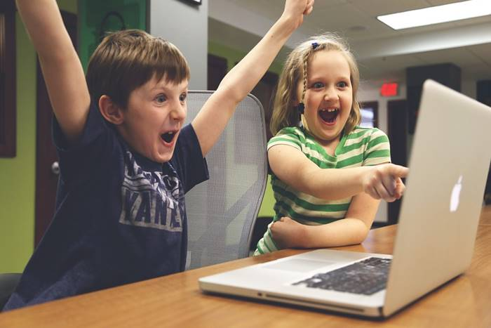Παιδιά μπροστά από λαπτοπ παίζοντας ηλεκτρονικό παιχνίδι