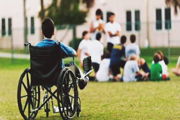 Παιδί με αναπηρία κοιτάει συμμαθητές του από μακριά