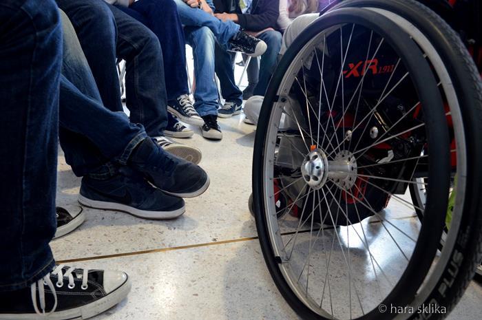 Αναπηρικό αμαξίδιο και πόδια μαθητών γύρω γύρω