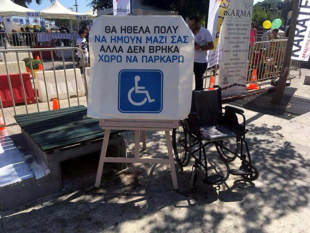 """Αναπηρικό αμαξίδιο με σύνθημα """"θα ήθελα πολύ να ήμουν μαζί σας αλλά δεν βρήκα χώρο να παρκάρω"""""""