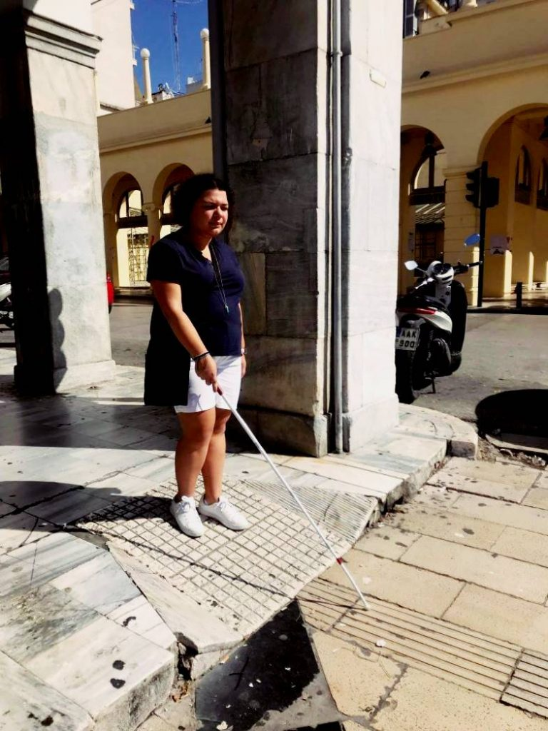 Η Μαρίνα περπατάει με το λευκό μπαστούνι πάνω σε οδηγό όδευσης τυφλών