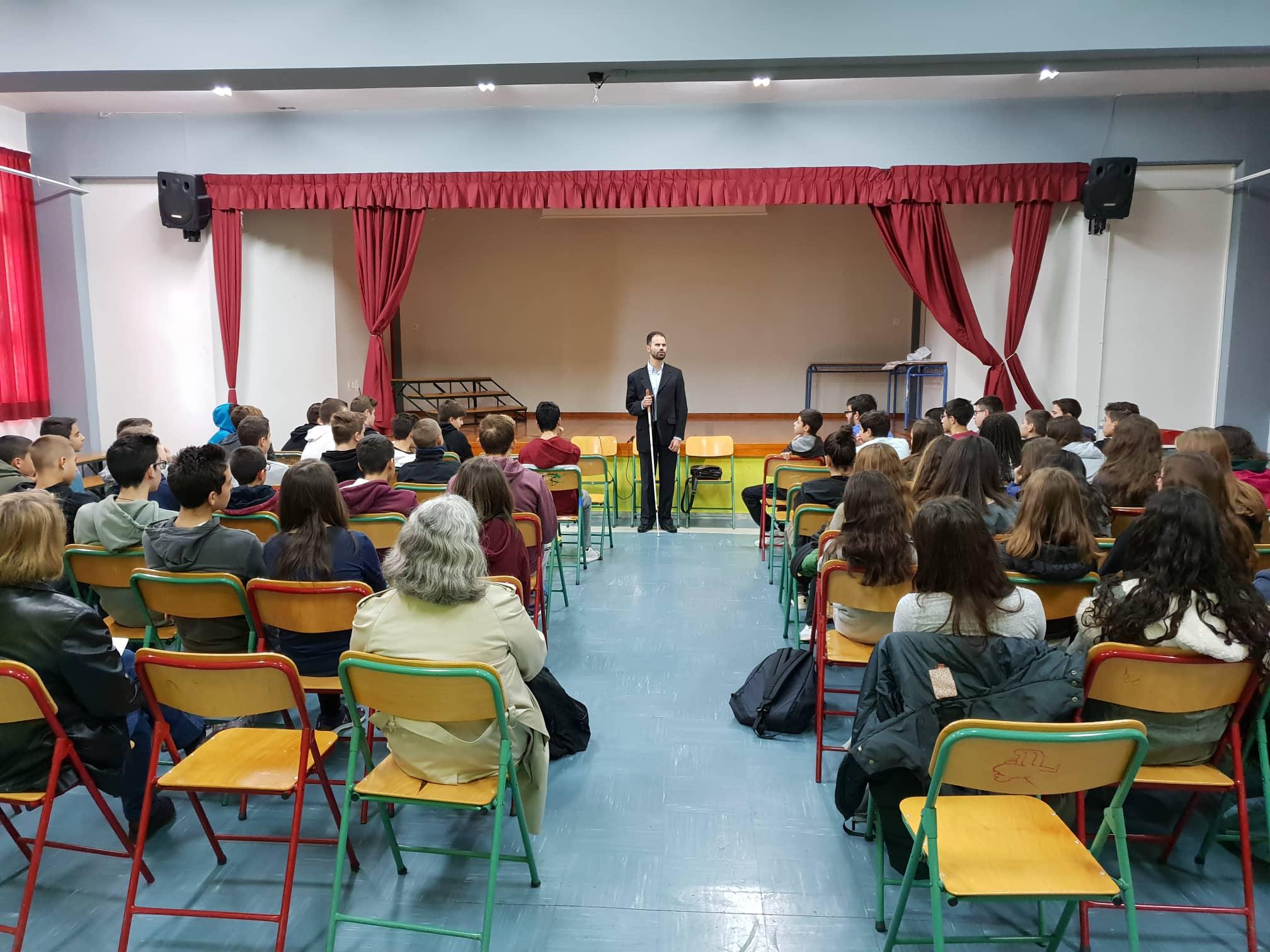 ο Βαγγέλης μιλάει στα παιδιά κρατώντας το λευκό μπαστούνι