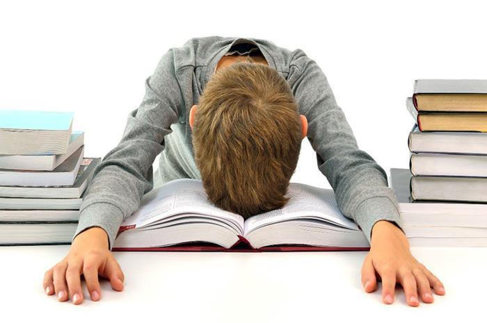 παιδί που έχει σκύψει το κεφάλι του πάνω στο βιβλίο