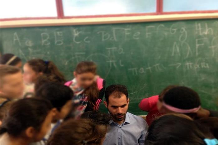Ο Βαγγέλης περιτρυγυρισμένος από παιδιά σε σχολείο