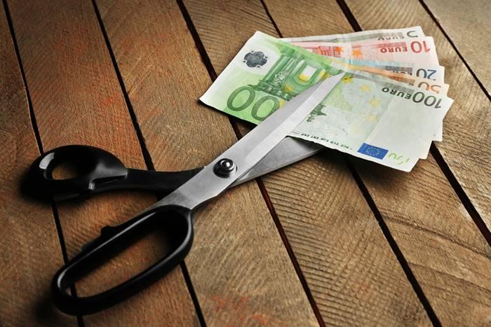 ένα ψαλίδι που κόβει χαρτονομίσματα των ευρώ