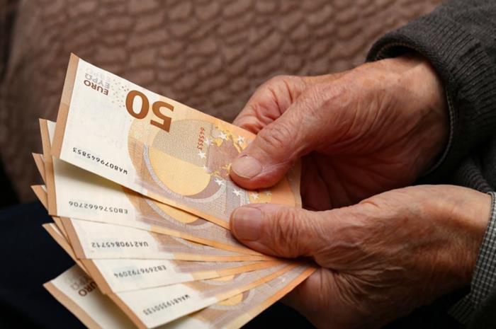 συνταξιούχος που κρατάει χαρτονομίσματα των 50 ευρώ