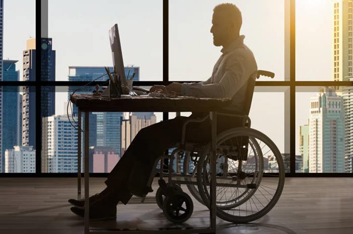 άνδρας σε αναπηρικό αμαξίδιο με λάπτοπο μπροστά του
