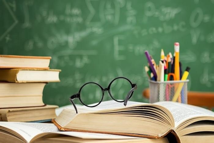 έδρανο με βιβλία, μολύβια, ένα ζευγάρι γυαλιά και στο βάθος ο πίνακας