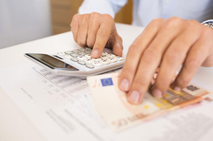 άνδρας με χαρτονόμισμα και αριθμομηχανή κάνει υπολογισμούς
