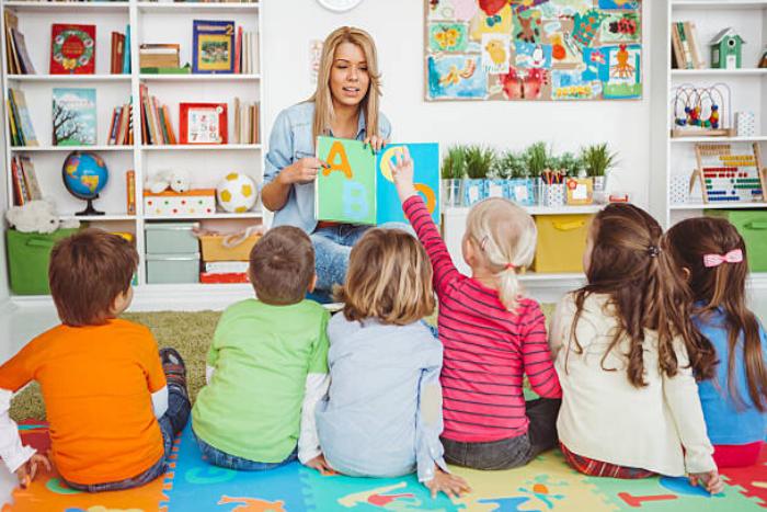 παιδιά στο νηπιαγωγείο και νηπιαγωγός κρατάει βιβλίο με αγγλικά γράμματα