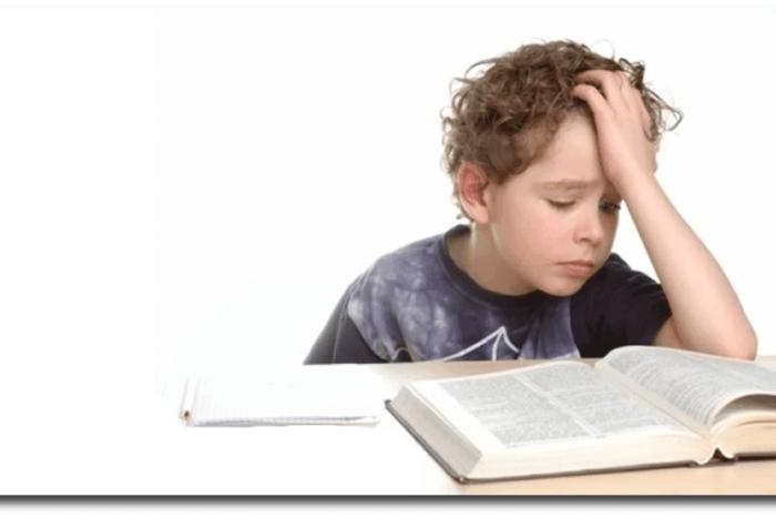 παιδί πάνω από βιβλία που κρατάει το κεφάλι του