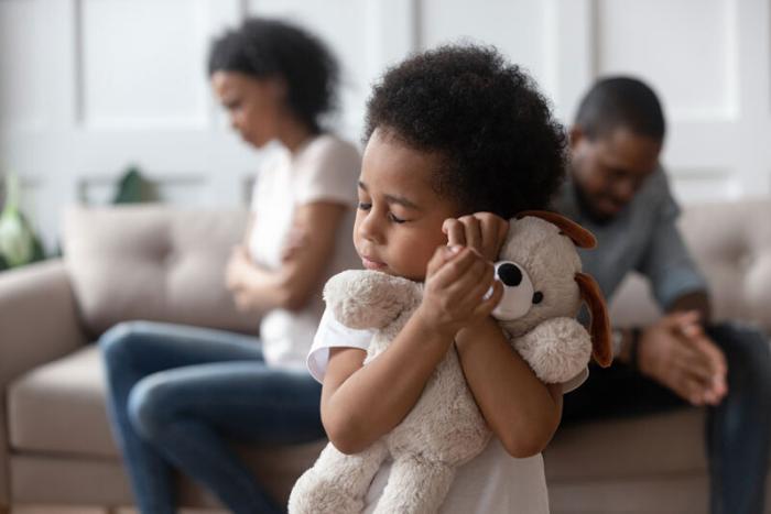 ένα παιδί που κρατάει σφιχτά ένα λούτρινο και πίσω γονείς που δεν μιλιούνται