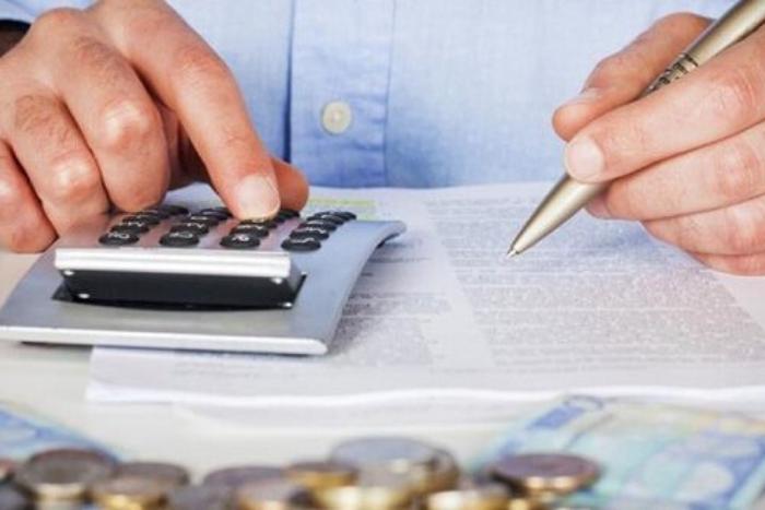 άνδρας με αριθμομηχανή και χρήματα μπροστά του κάνει υπολογισμούς