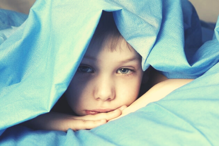 παιδί σε κρεβάτι κάτω από σεντόνια
