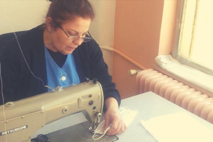 εργαζόμενη γυναίκα που ράβει μάσκες