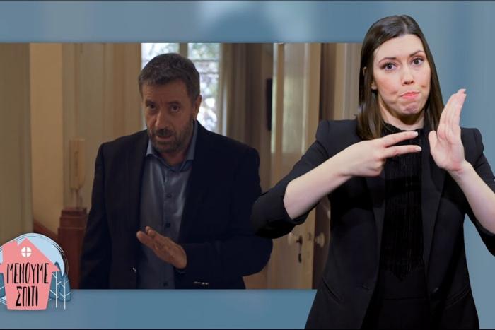"""Στιγμυότυπο από το τηλεοπτικό σποτ """"Μένουμε Σπίτι"""" ο Σπύρος Παπαδόπουλος και η διερμηνέας"""