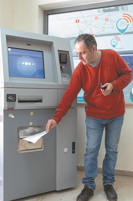 πολίτης σε ATM που βγάζει πιστοποιητικά