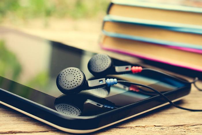 κινητό με ακουστικά και δίπλα βιβλία