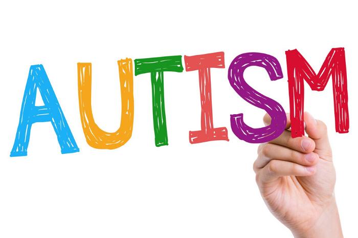 """χέρι που γράφει τη λέξη """"autism"""""""