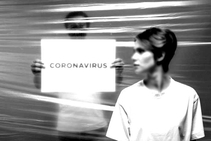 """άντρας με πλακέτα που γράφει """"coronavirus"""" και γυναίκα που κοιτάει"""
