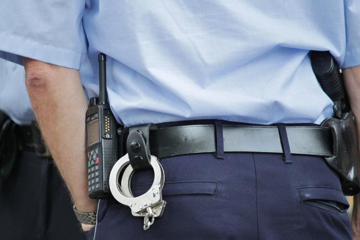 αστυνομικός πλάτη με χειροπέδες στη ζώνη