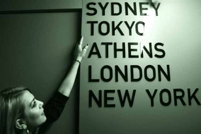 Μια γυναίκα που δείχνει πόλεις που είναι γραμμένες στον τοίχο Sydney, Tokyo, Athens, London, New York