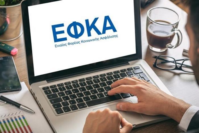 άνδρας σε λάπτοπ και στην οθόνη του λάπτοπ λογότυπο ΕΦΚΑ