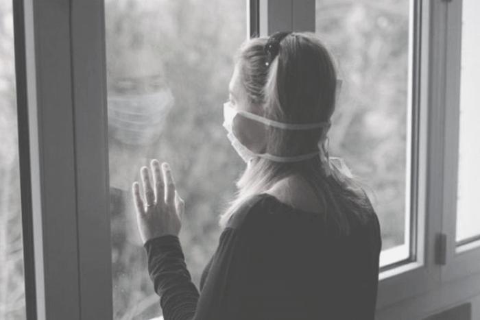 γυναίκα με μάσκα κοιτάει έξω από παράθυρο