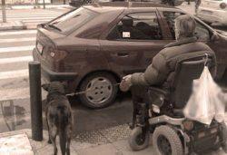 άνδρας σε αναπηρικό αμαξίδιο που δεν μπορεί να κατέβει πεζοδρόμιο γιατί είναι κλεισμένη η ράμπα από παρκαρισμένο
