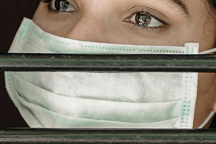 Γυναίκα πίσω από κάγκελα με μάσκα, φοβισμένη