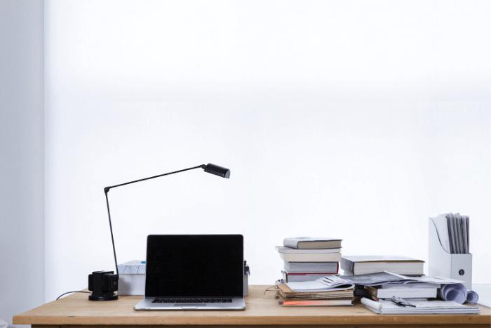 γραφείο εργαζόμενου με λάπτοπ και χαρτιά